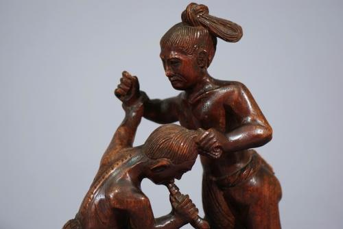 Hardwood carving of two wrestlers