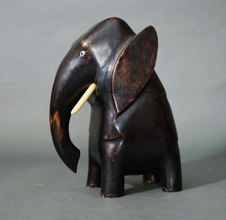 A ebonised hardwood elephant bottle holder