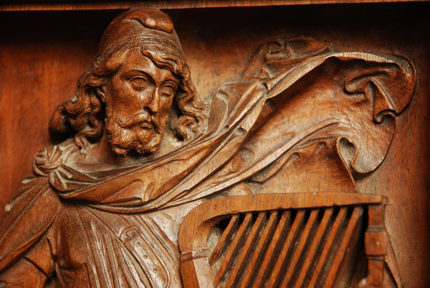 Thc carved walnut panel of medieval man in wood carvings