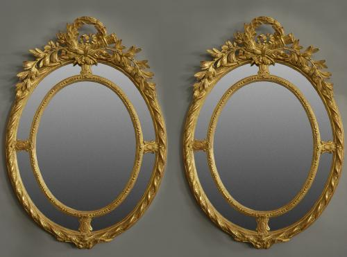 Pair of highly decorative oval gilt mirrors
