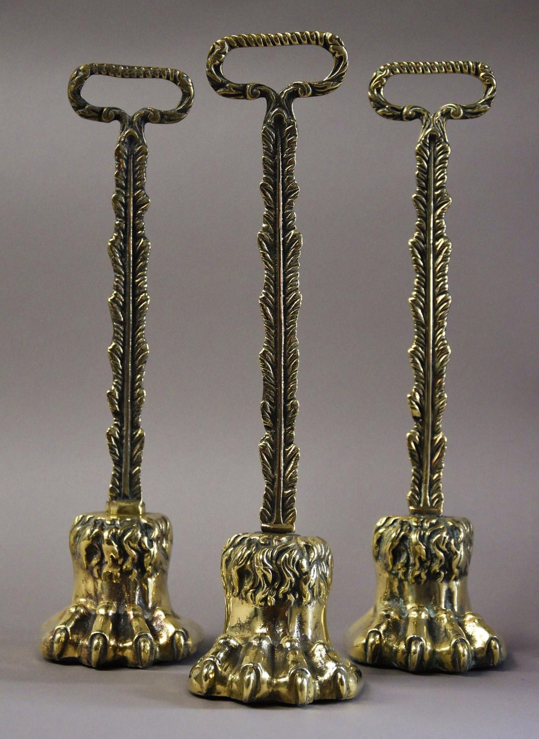 Three Regency brass lions paw door stops