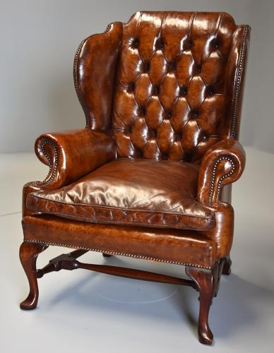 Early 20thc Georgian style deep buttoned brown leather wing armchair