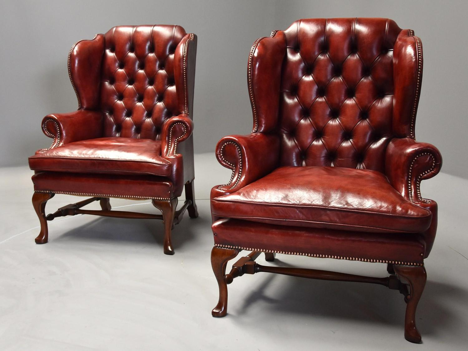 Pair of Georgian style deep buttoned red leather wing armchairs