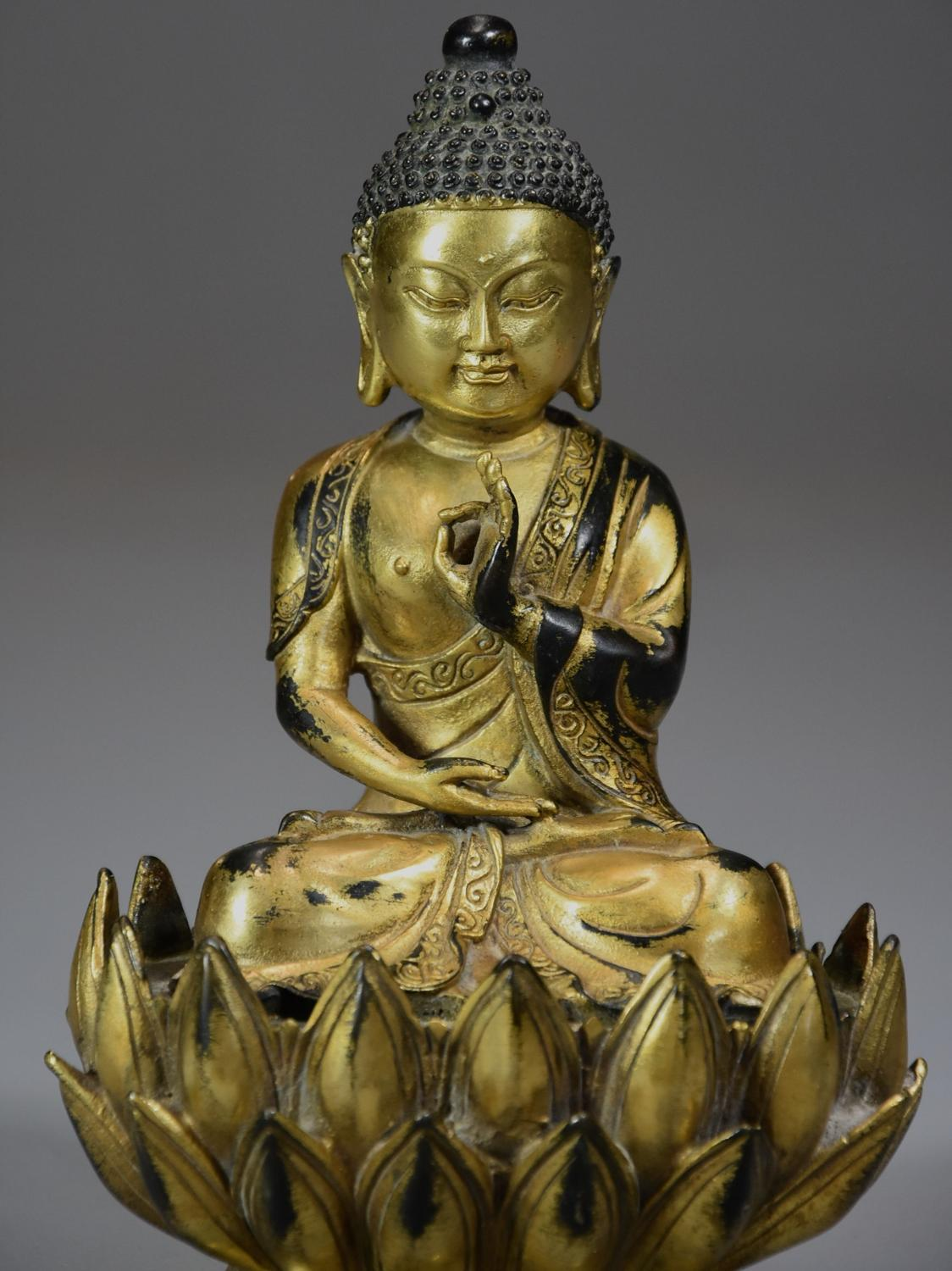 Superb quality gilt bronze Tibetan Buddha seated within a lotus flower